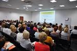 na zdjęciu widać osoby siedzące w sali konferencyjnej podczas spotkania